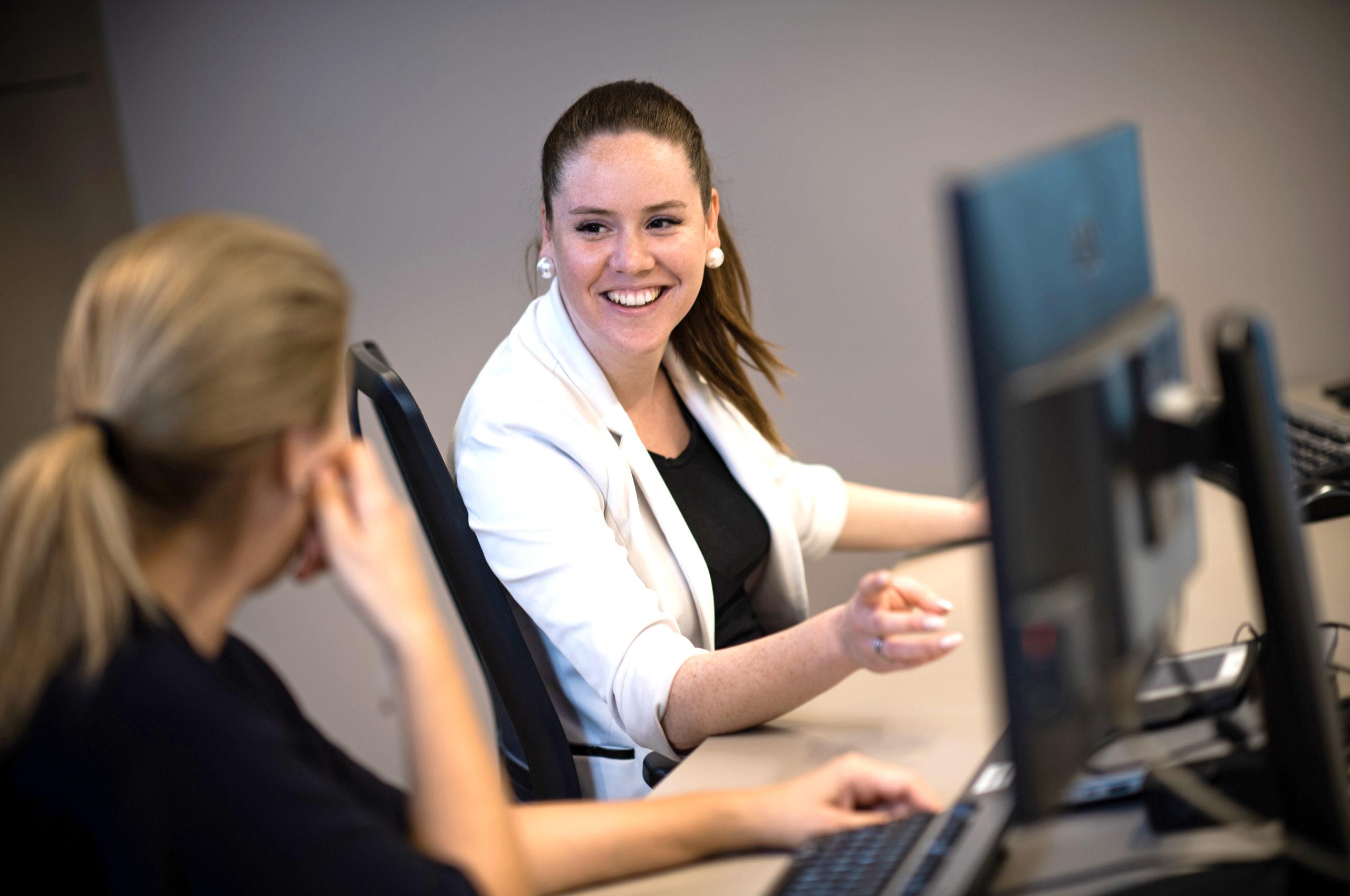 Zwei Frauen sitzen am Computer und unterhalten sich